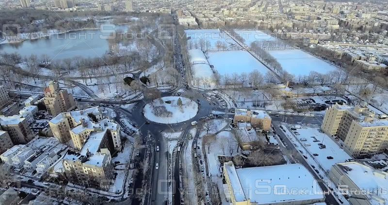 Aerial High Above Snowy Rooftops of Brooklyn Brownstones Prospect Park Football Fields Roundabout Winter NYC