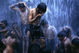 Shivite bathers under a waterfall photos