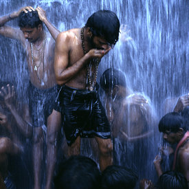 Shiva devotees bathing under a waterfall