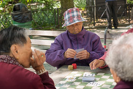 Old asian ladies playing card games on a game table at a park in Chinatown, New York.