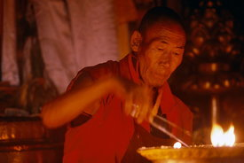 Monk lighting butter candles, Tashilhunpo