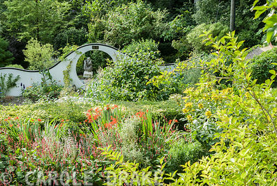 View from Wildly-Cheering Pavilion giving views over the herbaceous border and into the kitchen garden backed by undulating white wall containing moon gate. Beggars Knoll, Newtown, Westbury, Wiltshire, UK