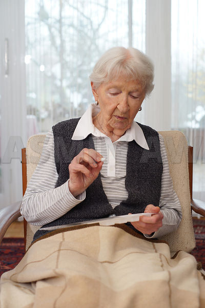 Senior lady taking medication at home