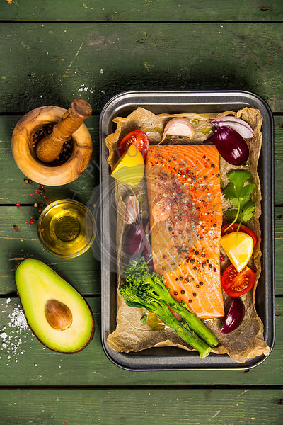 Baking dish with fresh raw salmon steak, vegetables  and seasoni