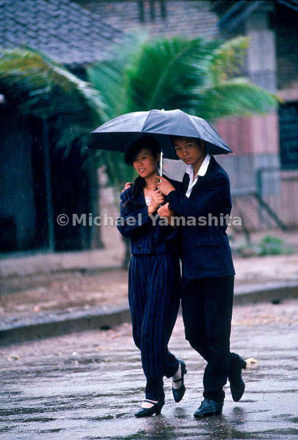 A single umbrella protects a fashionable young couple during rainy season in Jinghong. Yunnan, China