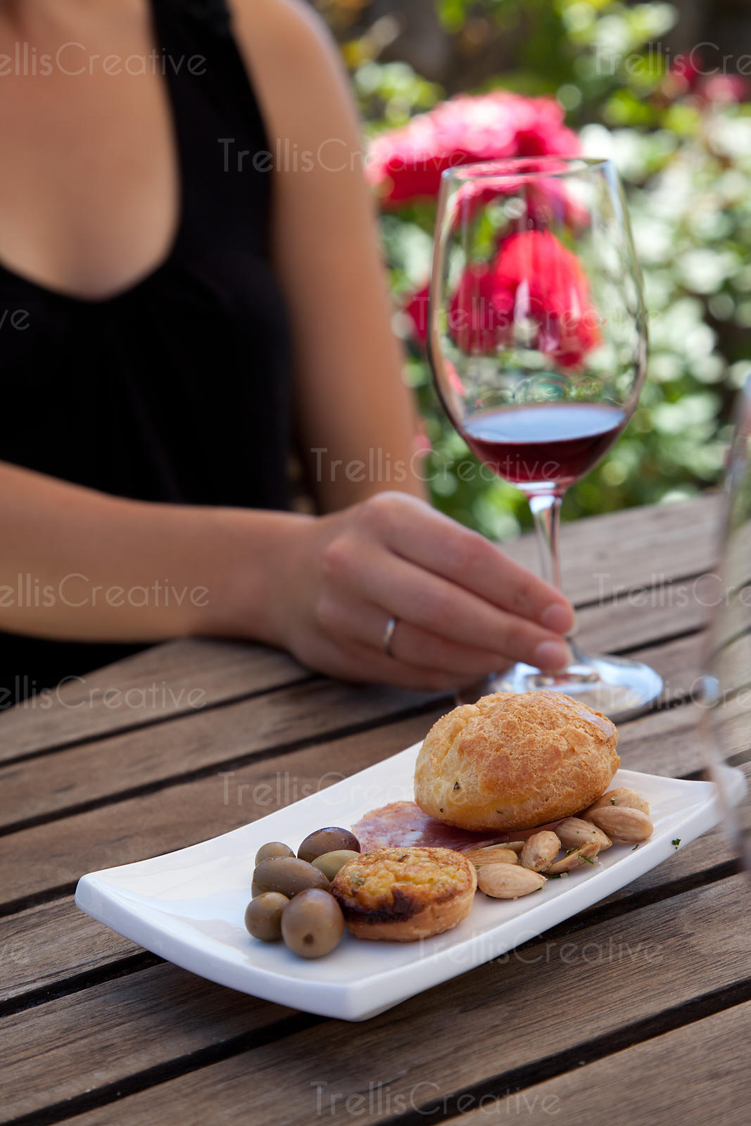 Young woman holding a glass or red wine at a wine and food pairing outdoors