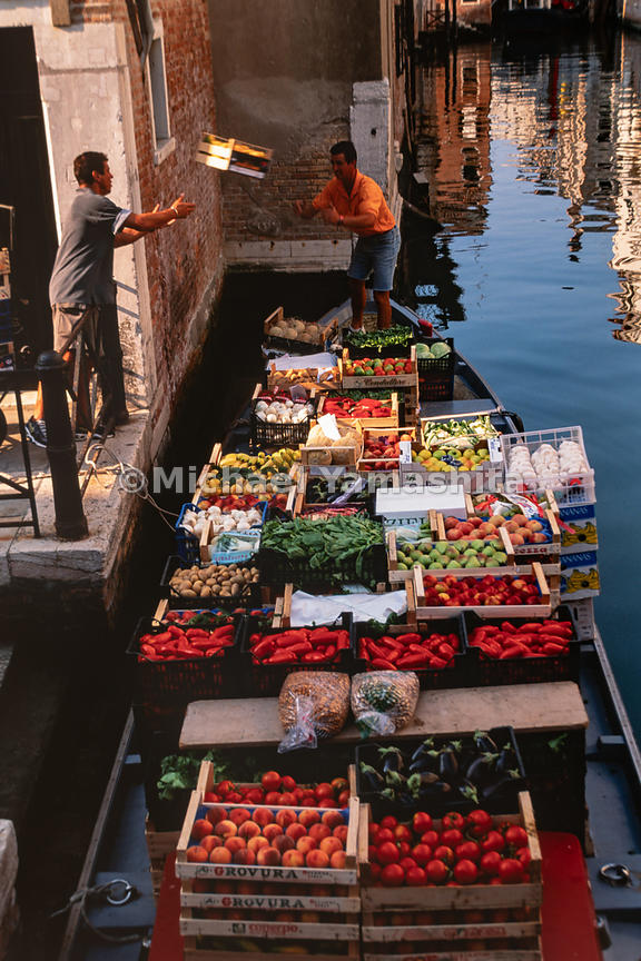 Tossing vegetables from boat to land is the fastest way of transporting produce. Venice, Italy, August, 1999.