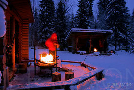 Wilderness shelters in winter and man by campfire