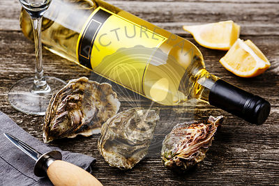 Oysters and bottle of wine on gray wooden background