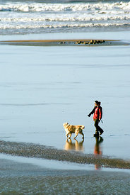 Woman walking dog, Rest Bay, Porthcawl, South Wales.
