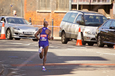 Britain's Mo Farah Running away from Camera with no other runners in sight in the London Marathon 2014