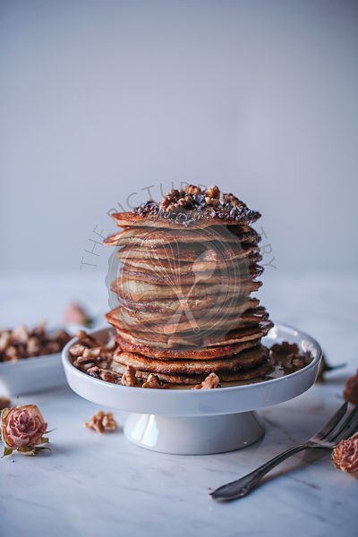 Stack of pancakes topped with maple syrup, walnuts and cacao nibs