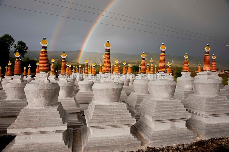 Colorful Stupas (Chorden, in Tibet) in Bame, Sichuan Province stand at attention, as if in awe of the fortuitous double rainbows arcing above during a sudden sun shower.