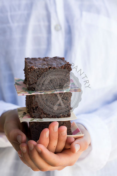 Girl Holding Stack of Chocolate Brownie.