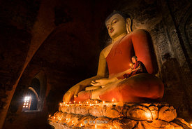 A young monk poses with a candle lit buddha in a temple in Bagan, Myanmar