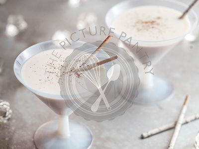 A light, bright image of 2 vintage milkglass martini glasses filled with Brandy Alexander.