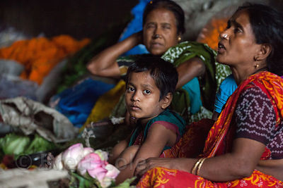 A girl works with her mother at the Howrah Flower Market, Kolkata, India.