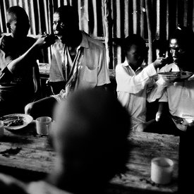 Hassan Fufona and another victim of the amputations are fed by boys af a cafe after begging. Freetown