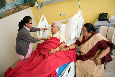 India - Delhi - A nurse makes a patient comfortable in bed