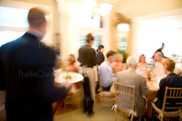 Waiters in motion serve food to dinner guests