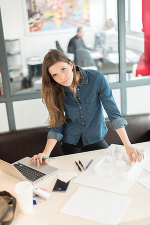 architect at office working on her laptop, looking at camera