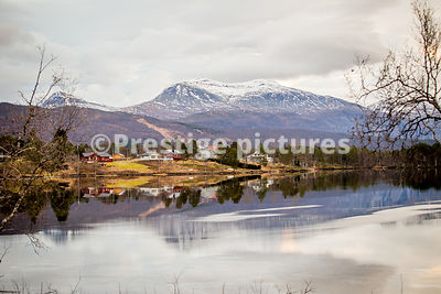 Small village community on the waters edge reflecting in a fjord with snow-capped mountain in the distance