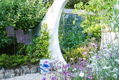 Moon gate framed by Geranium palmatum, Lychnis coronaria Oculata group, and Trachelospermum asiaticum, with copper 'talking heads' by Jon Ellis. Beggars Knoll, Newtown, Westbury, Wiltshire, BA13 3ED, UK
