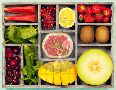 Vegetables and fruits in wooden box for vegan, gluten free, allergy-friendly, clean eating and raw diet. Blue background and top view