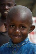 Young African boy smiling at camera with blue shirt on, western Kenya Africa