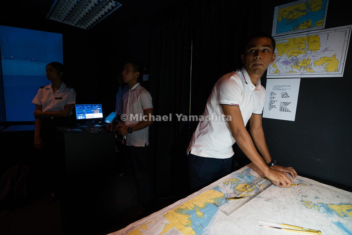 A future maritime officer keeps his eyes peeled to the screen. Spread out across a large table, printed nautical charts allow maritime trainees to mark the ships position and determine the best course of action in any given scenario.