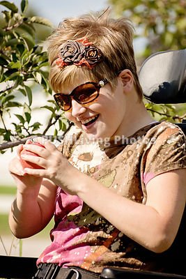 Young woman in a wheelchair picking apples