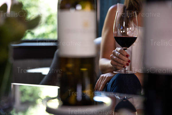 Close-up of a woman holding a glass of red wine in her hand while sitting