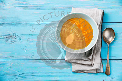Pumpkin soup on blue wooden background Copy space