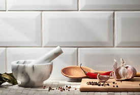 Marble pestle with spices on white ceramic background