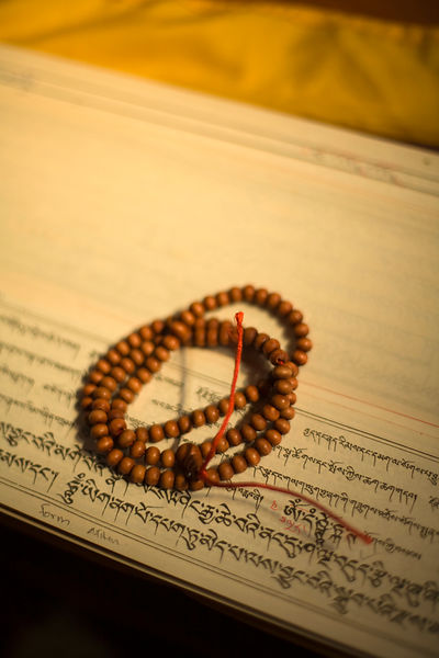 India - Sarnath - Buddhist prayer beads sit on top of sutras