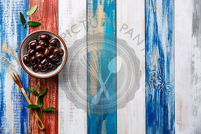 Kalamata olives and fork on wooden background