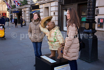 Tourists Posing with a Statue of Paddington Bear the Explorer in a Central London Street