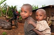 Two Rwandan brothers, eldest carrying the youngest on his back. Rwanda
