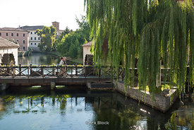 People walking on a bridge in Portogruaro, Italy.
