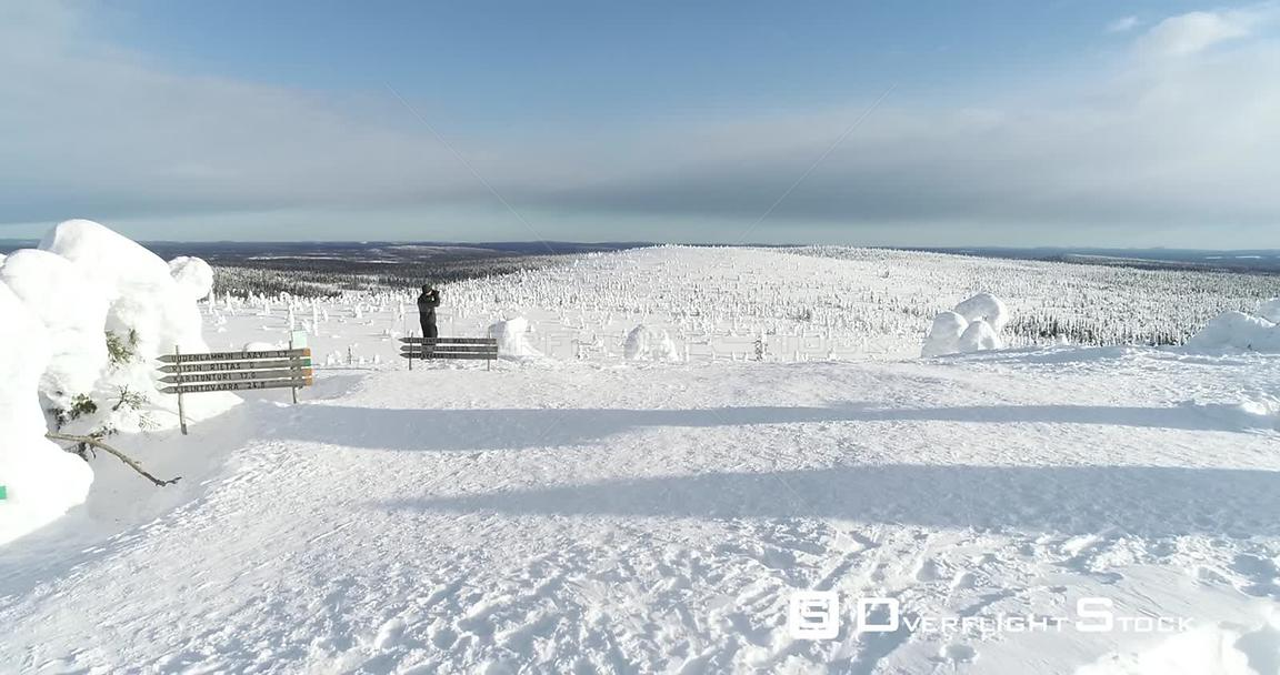 Man Hiking, Snowy Mountain, 4k Aerial View Bypassing a Man Taking Pictures on the Top of a Fjeld Tunturi, Full of Snow Covered Trees, Riisitunturi National Park, Lapland, Finland