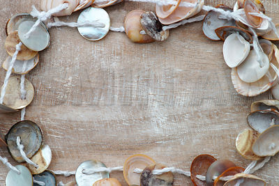 Small shells necklace on wood background with copy space