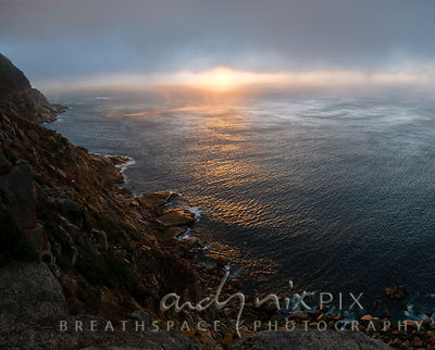 Sunset over sea under low cloud, rocky coastline and cliffs