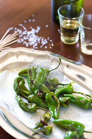 padron peppers as a typical Spanish tapas style snack on wood table , with sherry glasses and bottle in background