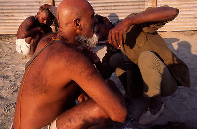 A barber trims the beard of a Saddhu at the Ardh Kumbh Mela 1995, Allahbad, India