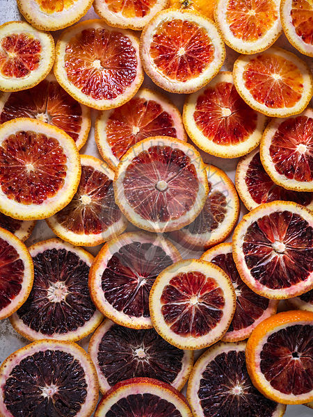 Sliced blood oranges in ombre pattern, full bleed.