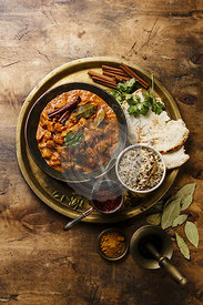 Chicken tikka masala spicy curry meat food in copper pan with rice and naan bread on wooden background
