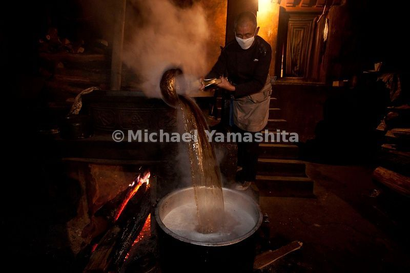 Litang Monastery, butter tea making and serving. Tea used to be churned using a washing machine but today they use an electric drill with a long propeller like bit. ....................................
