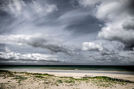 Single wave breaking on a flat sea, deserted beach, storm clouds