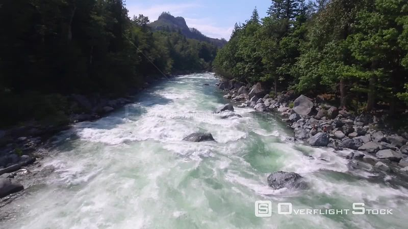 Backing aerial view of whitewater rapids and mountainous river valley with lush evergreen forest. Index Washington State