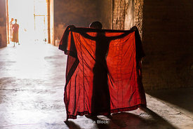 A yong novice priest adjusts his robes at a temple in Bagan, Shan State, Myanmar.